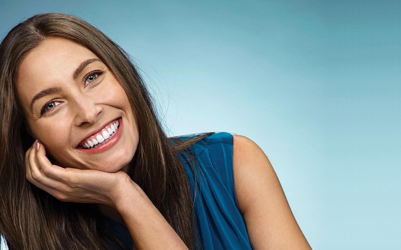 Χαμογελαστή γυναίκα δείχνει τα ίσια δόντια μετά από ορθοδοντική θεραπεία στην Ορθοδοντική Κλινική Σανούδος Καπακιάν Γλυφάδα