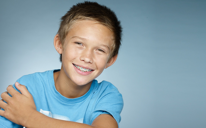 Χαμογελαστό αγόρι με χρωματιστά σιδεράκια για παιδιά από τη Σανούδος-Καπακιάν Ορθοδοντική Κλινική στη Γλυφάδα