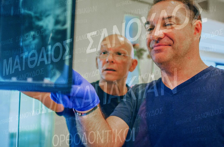 Οι ορθοδοντικοί Σανούδος&Καπακιάν εξετάζουν ακτινογραφία στην Ορθοδοντική Κλινική Σανούδος-Καπακιάν στη Γλυφάδα