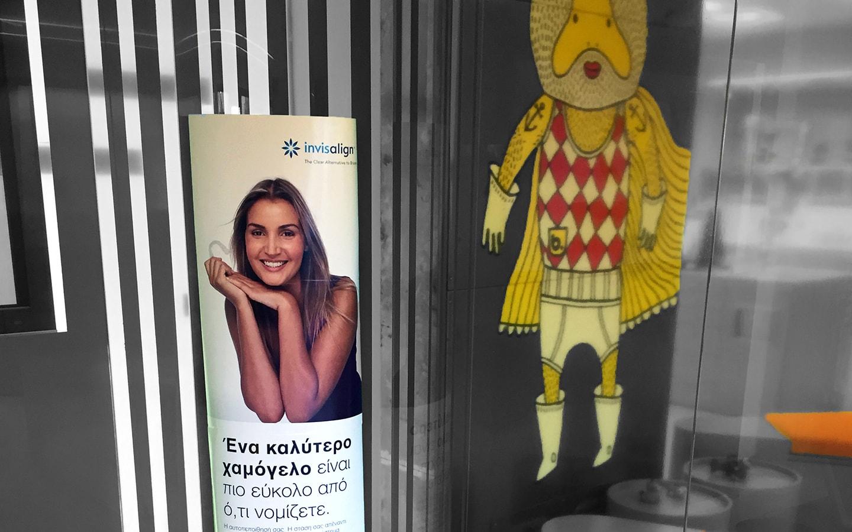 Διαφήμιση θεραπείας Invisalign στο εσωτερικό της Ορθοδοντικής Κλινικής Σανούδος -Καπακιάν στη Γλυφάδα