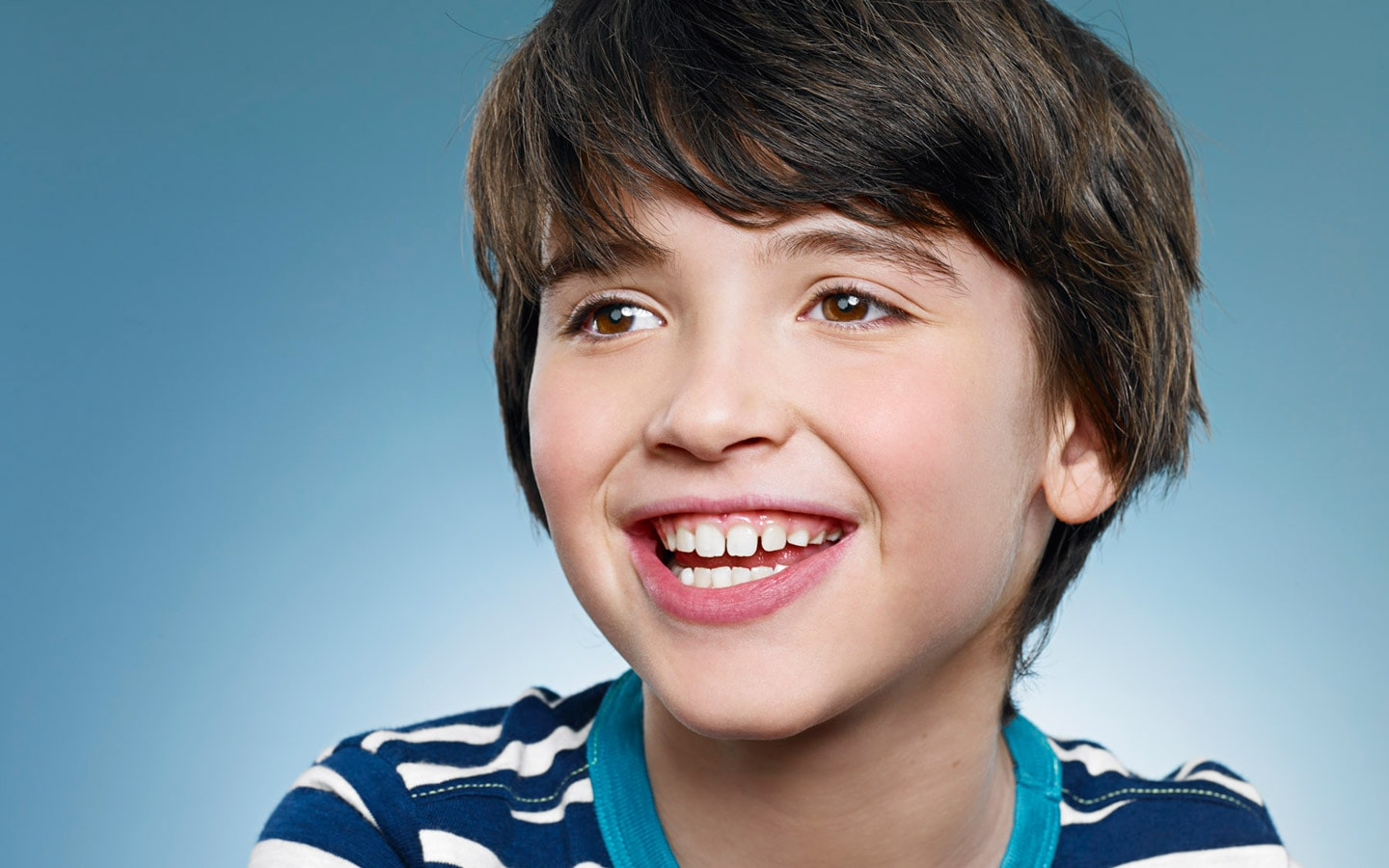 A smiling boy is ready for Sanoudos Kapakian orthodontic braces treatment to straighten his teeth