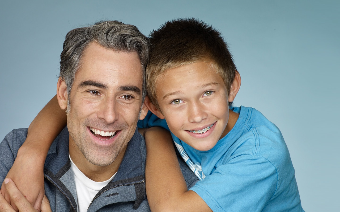 A boy with braces & his dad having had treatment at the Sanoudos Kapakian Clinic in Glyfada, Athens