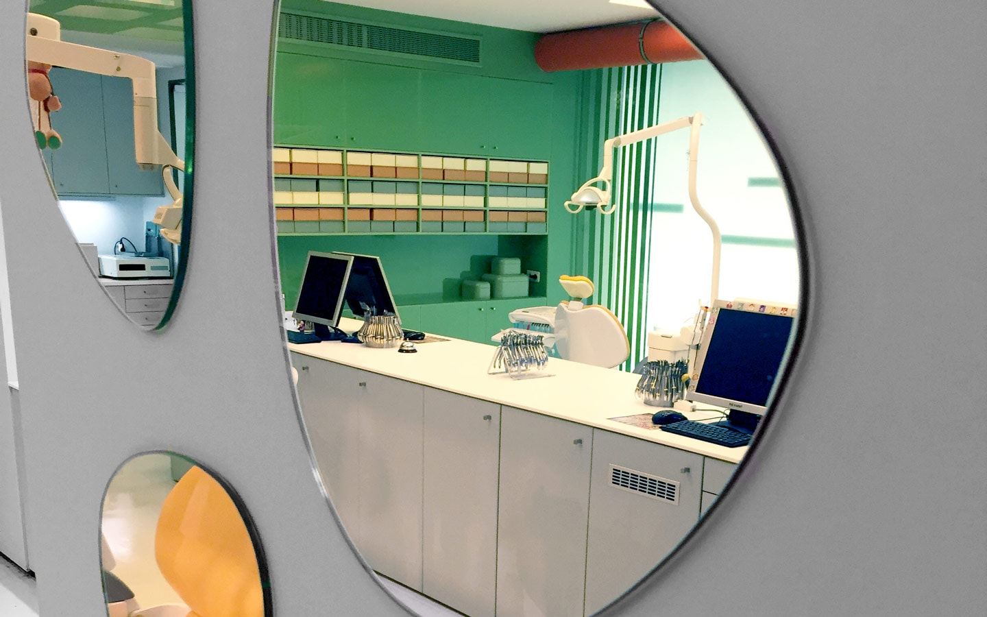 Desk, computers & light reflected in mirror in the Sanoudos Kapakian orthodontic practice in Glyfada